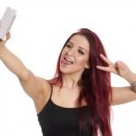 Rothaarige Frau macht ein Selfie und zeigt Victory