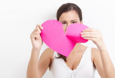 8559652 - young woman pulling pink paper heart to pieces.