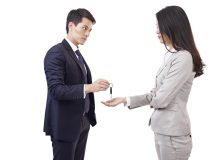 angry man handing car key to unhappy woman