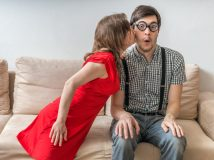 Shy man is surprised by kiss from woman sitting on sofa. Dating concept.